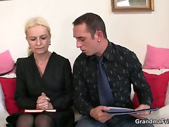 Old blonde sucks on two hard cocks at the office