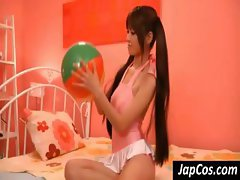 Cute Asian girl plays with a ball and rubs her pussy with panties on